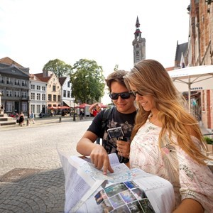 A man and a woman looking at a map in the city centre of Bruges, Belgium